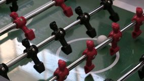 Board game of football soccer. Foosball. Closeup of the hand of a child throwing the ball on the field with football. Board game of football. Closeup of the hand stock footage