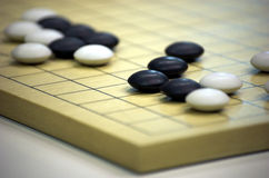 Board game Go. Detail of a board with stones for the ancient strategy table game of go Royalty Free Stock Images