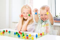 Little blonde girl and boy have fun, laugh and indulge playing board game. Hold people figures in hands. yellow, blue, green wood. Board game and kids leisure stock photography