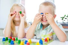 Little blonde girl and boy have fun, laugh and indulge playing board game. Hold people figures in hands like their eyes. yellow, b. Board game and kids leisure stock photos