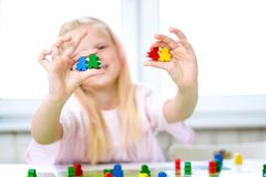 Little blonde girl have fun, laugh and indulge playing board game. Hold people figures in hands . yellow, blue, green wood chips - royalty free stock images