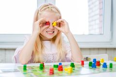 Little blonde girl have fun, laugh and indulge playing board game. Hold people figures in hands like her eyes. yellow, blue, green. Board game and kids leisure royalty free stock image