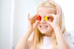 Little blonde girl have fun, laugh and indulge playing board game. Hold people figures in hands like her eyes. yellow and red wood. Board game and kids leisure stock photography