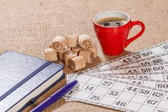 Board game lotto on sackcloth. Wooden lotto barrels and game cards with a cup of coffee and a notebook. Board game lotto on sackcloth. Wooden lotto barrels and royalty free stock photos