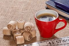 Board game lotto on sackcloth. Wooden lotto barrels and game cards with cup of coffee, notebook and pen. Board game lotto on sackcloth. Wooden lotto barrels and stock image