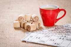 Board game lotto on sackcloth. Wooden lotto barrels and game cards with cup of coffee. Board game lotto on sackcloth. Wooden lotto barrels and game cards for a stock photos