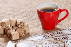 Board game lotto on sackcloth. Wooden lotto barrels and game cards with cup of coffee. Board game lotto on sackcloth. Wooden lotto barrels and game cards for a royalty free stock images