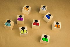 Board game pawn on top of wooden cube with other ones fallen against color background royalty free stock photo