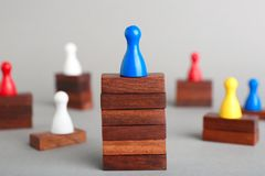 Board game piece on wooden blocks dominating other figures against grey background. Victory concept stock photos