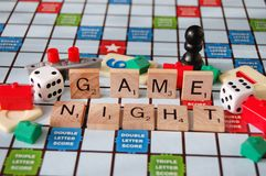 Board Games Family Fun Night. Board game pieces and the word game night written in scrabble letters royalty free stock photo