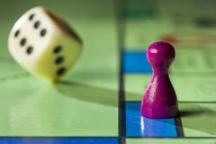 Board game with rolling dice. Close up of a board game with pawn and  rolling dice Royalty Free Stock Photography