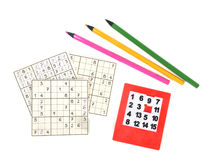 Board games. Cards, games, rebuses, pencils lie on a table Stock Photos