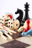 Board games. Detail of board games, pawns, chessmen, mikado and dices on chess board royalty free stock photo