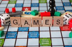 Board Games Family Fun Night. Board game pieces and the word games written in scrabble letters stock images