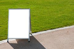 Board on grass. Empty metallic board next to a grass field (isolated on white, focus on the grass Royalty Free Stock Photo
