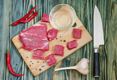 Board knife meat peppers. A piece of fresh meat on a cutting board with a knife and pepper Stock Photography