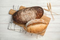 Board with loaves of bread on wooden table. Top view stock photos