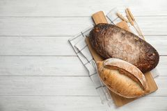 Board with loaves of bread on wooden table. Space for text. Board with loaves of bread on wooden table, top view. Space for text stock photography