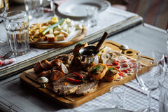 Board with meat. Wooden Board with meat slices and water glasses Royalty Free Stock Photos