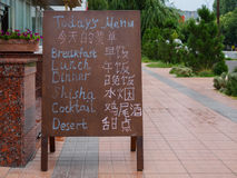 Board with menu on english and korean languages near restaurant Stock Images