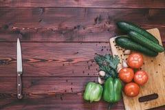 board nya grönsaker för cuttingen tomat gurka, spansk peppar, vitlök, kryddor royaltyfria bilder