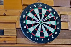 Board for playing darts on a wooden wall close up stock photos