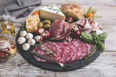 Board with prosciutto, salami,bacon and cheese mozzarella ,brie,olives,home bread Royalty Free Stock Images