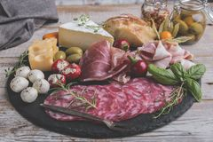 Board with prosciutto, salami,bacon and cheese mozzarella ,brie,olives,home bread Stock Images