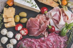 Board with prosciutto, salami,bacon and cheese mozzarella ,brie,olives,pickles Stock Photos