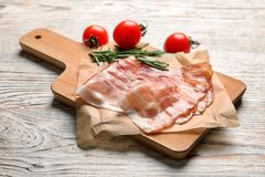 Board with raw bacon rashers. On wooden background Stock Photography
