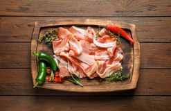 Board with raw bacon rashers. On wooden background Royalty Free Stock Photography