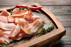 Board with raw bacon rashers on table. Closeup Royalty Free Stock Image