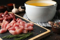 Board with raw meat fondue pieces and rosemary. On table royalty free stock images