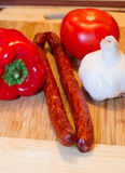 Board with sausages and vegetables. Some vegetables - pepper, garlic and tomato with sausages on a kitchen board Royalty Free Stock Images
