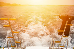 On-board the ship on the background ship trail waves and sunset. Stock Image