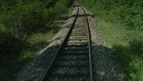 A train passing through some woods. A on board shot of a train passing through some woods stock footage