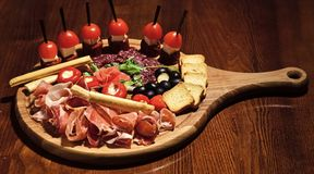 Board with snacks on wooden table. Snacks appetizing served on round board. Restaurant dish concept. Cold appetizers. With tomatoes, sausage, salami, ham stock photo