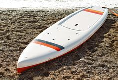Board for stand up paddle surfing SUP. On beach at sea waves background stock photo