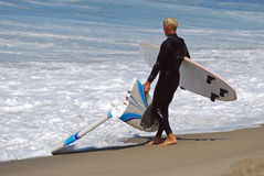 Board surfer hauls in a broken board at Aliso Beach, Laguna Beach, CA. Royalty Free Stock Images