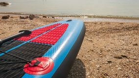 Board for swimming with a paddle on the shore of the blue sea on a clear. Summer day royalty free stock image