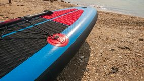 Board for swimming with a paddle on the shore of the blue sea on a clear. Summer day stock image