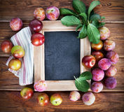 Board for text with fresh plums and green leaves Royalty Free Stock Image