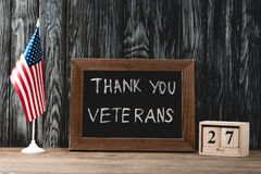 Board with thank you veterans lettering near american flag and cubes with date