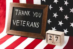 Board with thank you veterans lettering near flag of america and cubes with date