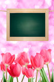 Board and tulips on a pink background of heart. Stock Photo