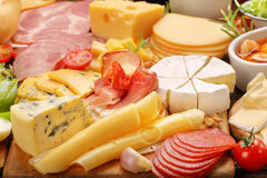 Board of various types of cheese and appetizers set. On rustic wooden board royalty free stock photos