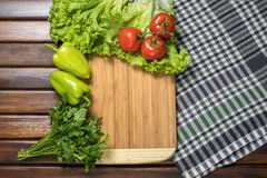 Board with vegetables on table Stock Photos