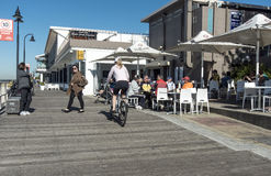 Board walk cafe brighton le sands. With the beach on the left and people enjoying breakfast and cyclist riding by Stock Photo