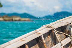 Board of a wooden boat close-up and splashing water. Overboard Stock Images