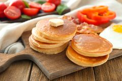 Board with yummy pancakes. On wooden table Stock Photos